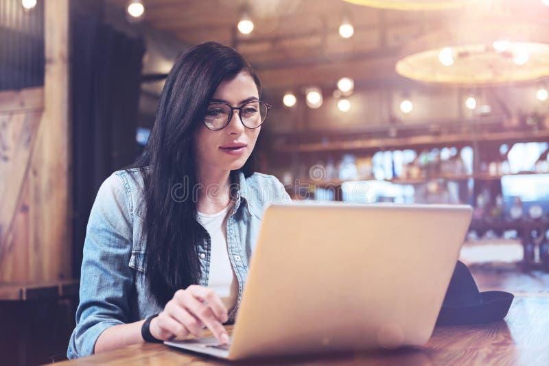 Bella donna astuta che lavora al computer portatile fotografie stock libere da diritti