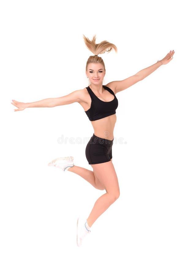 Bella donna attiva in un salto di usura di forma fisica isolata sopra fondo bianco immagine stock libera da diritti