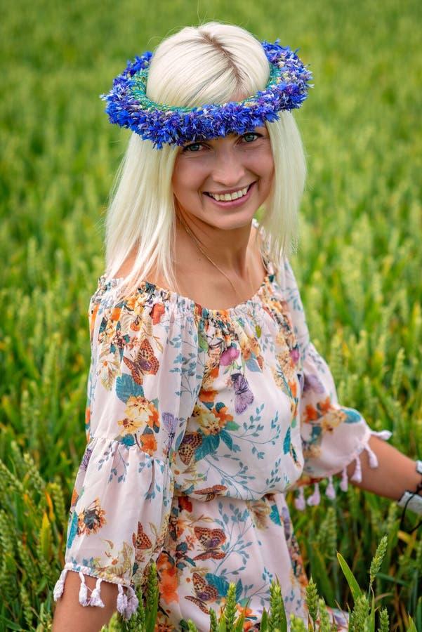 Bella, donna attraente e bionda con la corona blu del fiordaliso nel campo dei cereali immagine stock libera da diritti