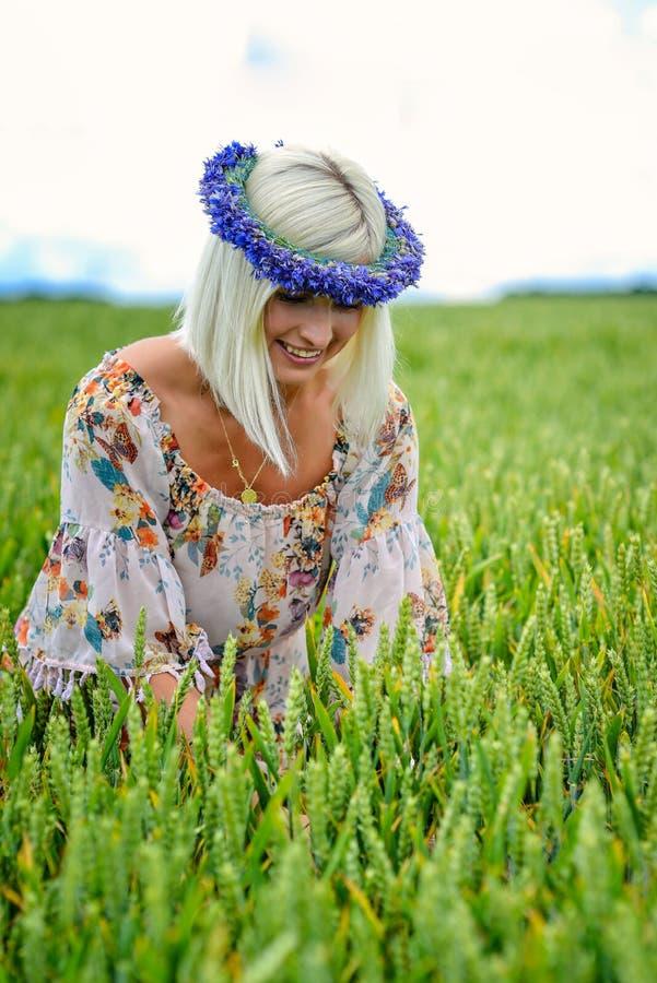Bella, donna attraente e bionda con la corona blu del fiordaliso nel campo dei cereali fotografia stock libera da diritti