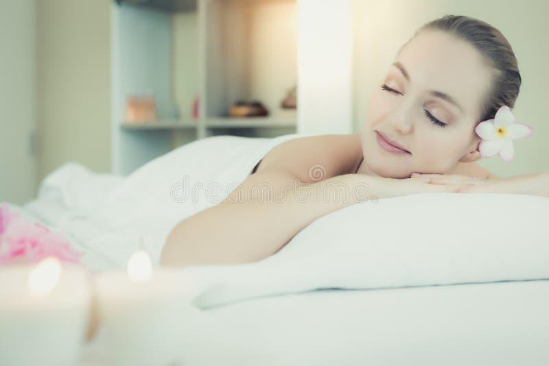 Bella donna attraente sdraiare sul letto al salone della stazione termale La bella ragazza incantante ottiene rilassantesi, felic fotografie stock