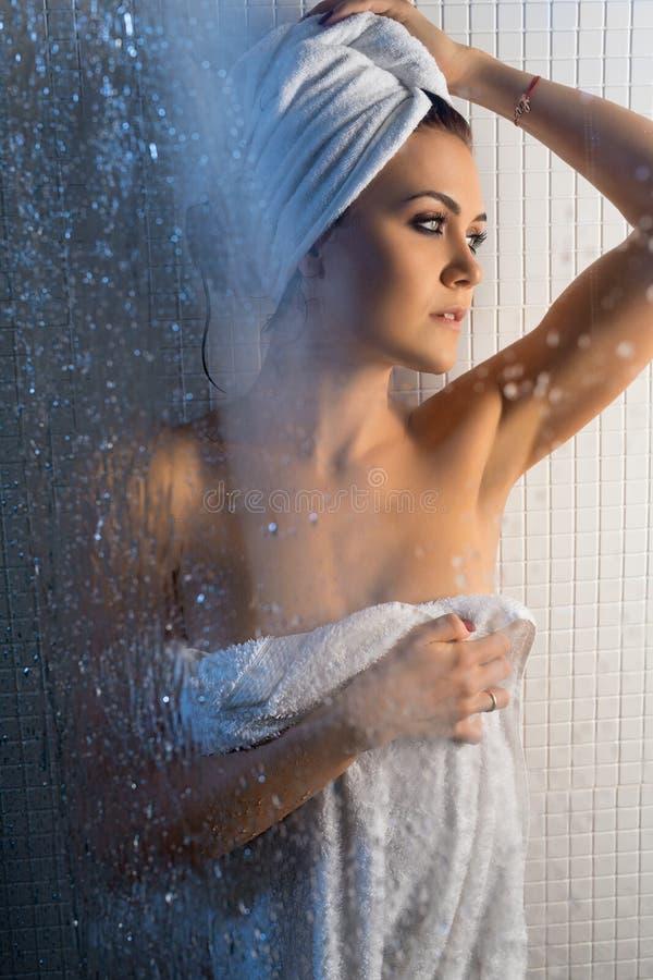 Bella donna avvolta in asciugamano che ha doccia immagine stock