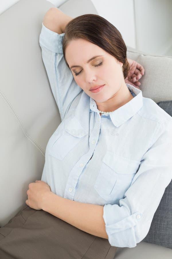 Bella donna ben vestito che riposa sul sofà fotografia stock libera da diritti