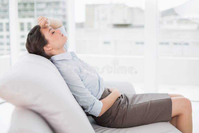 Bella donna ben vestito stanca che si siede sul sofà a casa fotografia stock