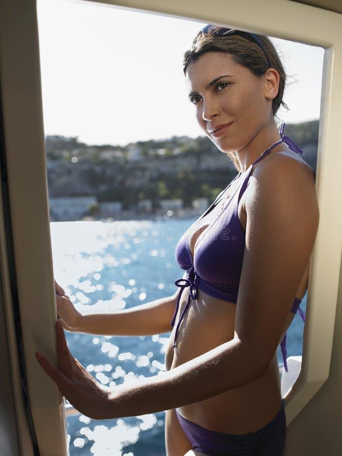 Bella donna in bikini che sta sull'yacht fotografie stock
