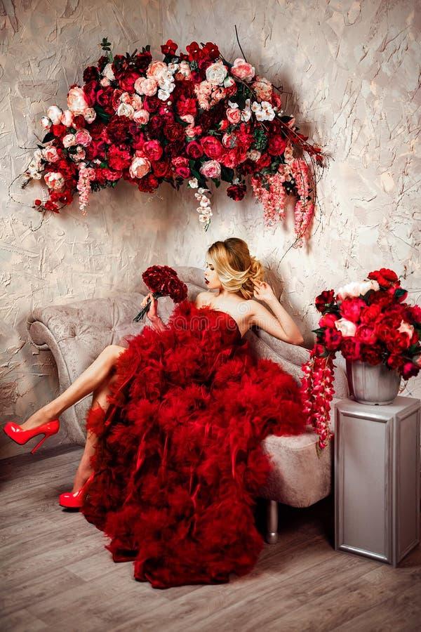 Bella donna bionda alla moda sexy sul sofà immagini stock libere da diritti