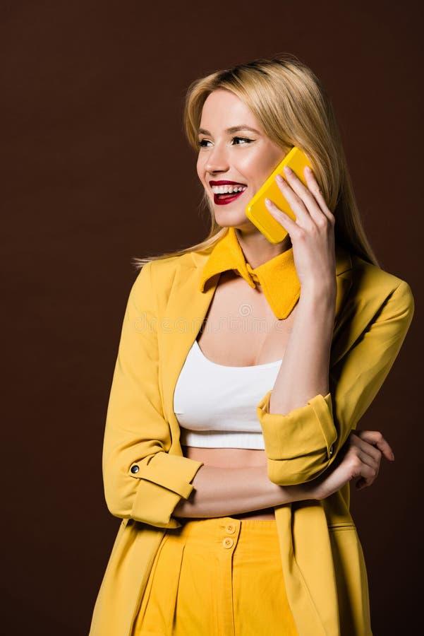 bella donna bionda allegra che parla lo smartphone giallo e distogliendo lo sguardo immagine stock