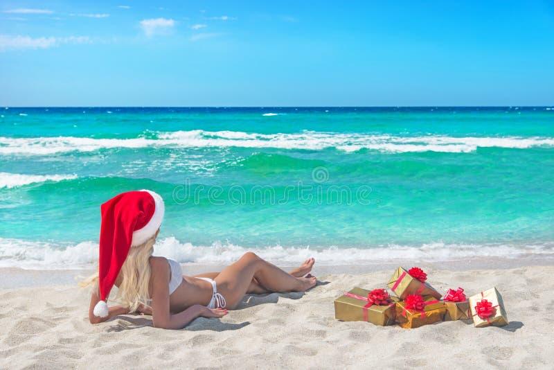Bella donna bionda in bikini, cappello rosso di natale e contenitore di regalo fotografia stock libera da diritti