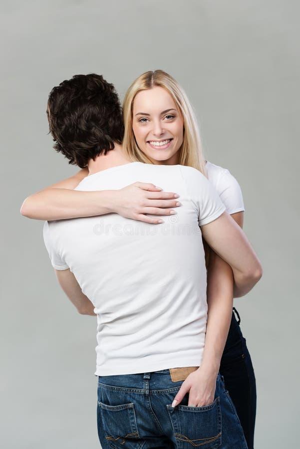 Bella donna bionda che dà al suo marito un abbraccio fotografie stock libere da diritti