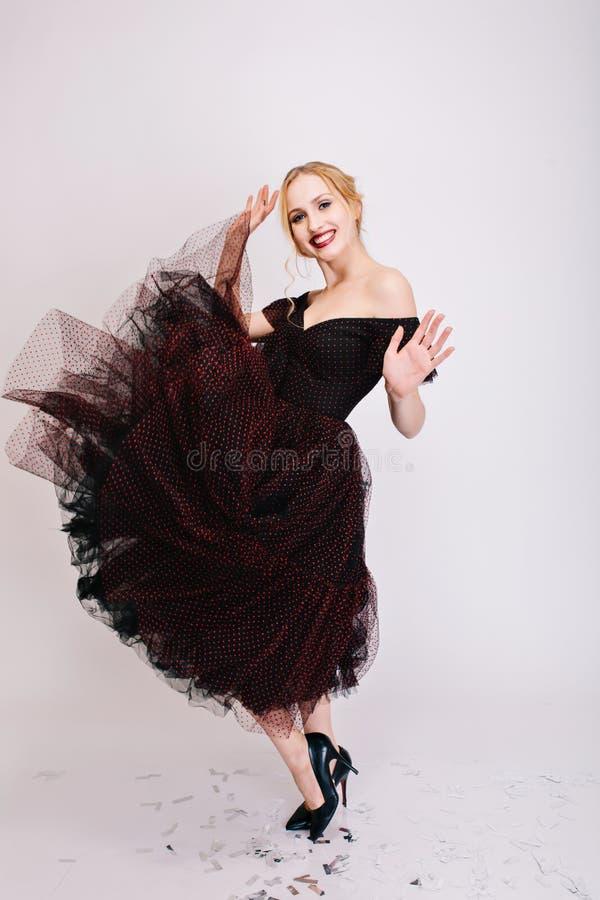 Bella donna bionda che fila nel ballo, volteggiando gonna, divertendosi al partito, godente del tiro in studio con bianco fotografia stock