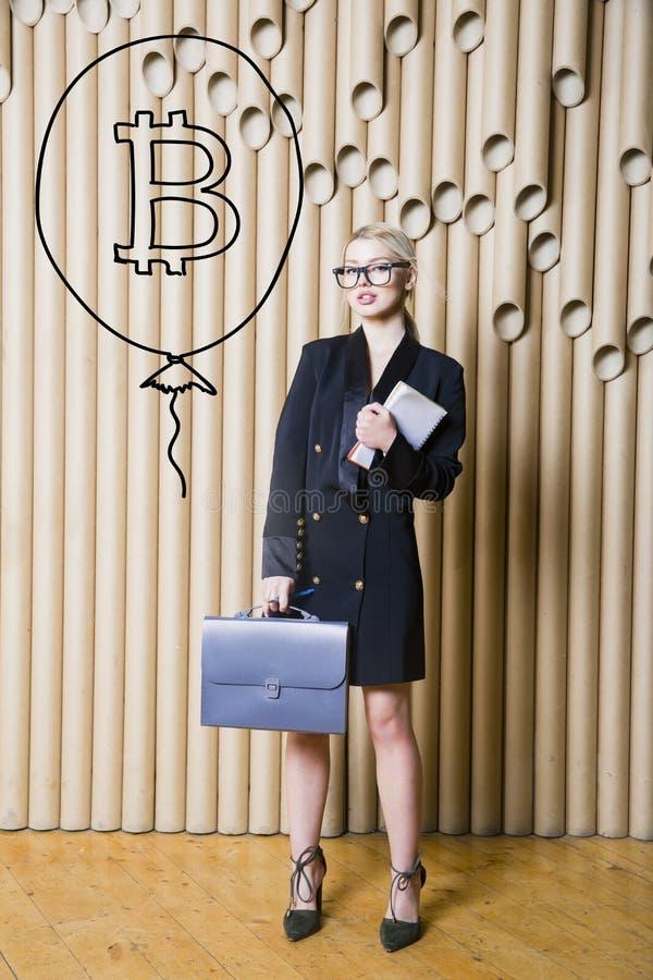 Bella donna bionda che mostra schizzo vicino diritto del bitcoin Concetto virtuale di schiacciamento del btc o dei soldi Cryptocu fotografia stock libera da diritti
