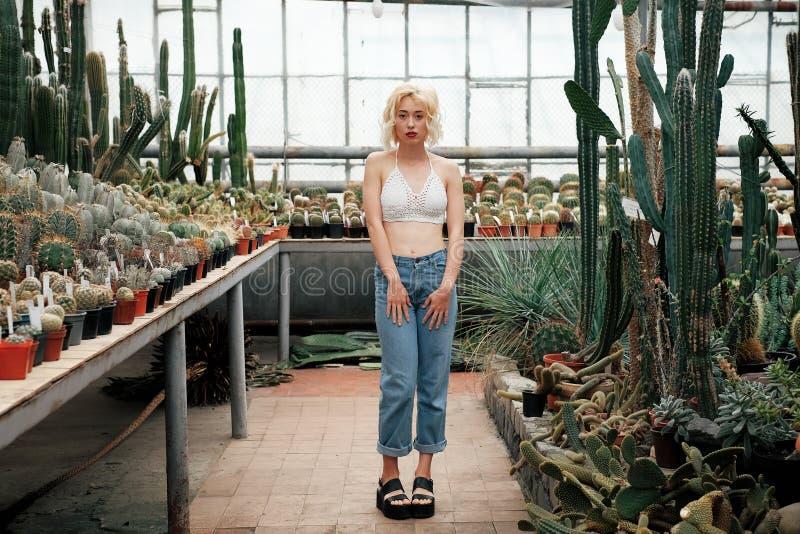 Bella donna bionda che posa nel giardino botanico tropicale fotografia stock libera da diritti