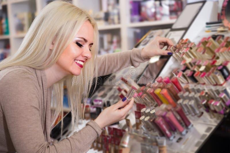 Bella donna bionda che sceglie labbro più grassoccio su esposizione fotografia stock