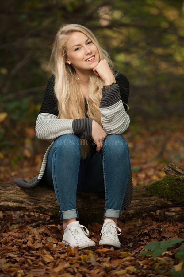Bella donna bionda che si siede sulla seduta su una connessione della foresta in autunno fotografia stock