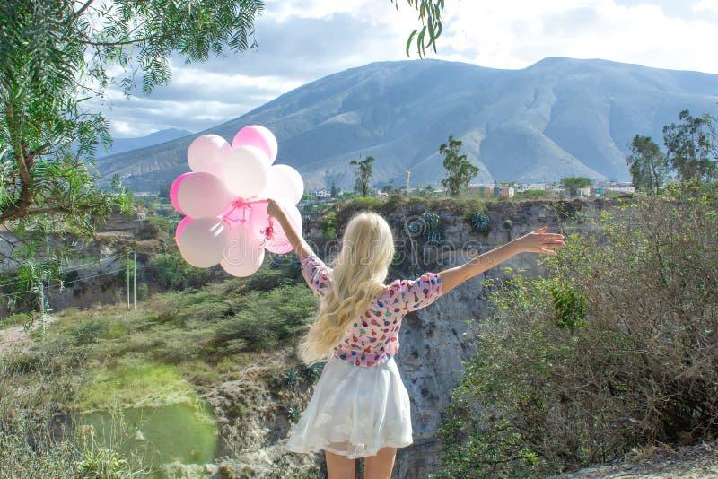Bella donna bionda che sta e che esamina un bello paesaggio e le montagne E tiene i palloni rosa in sua mano immagini stock libere da diritti