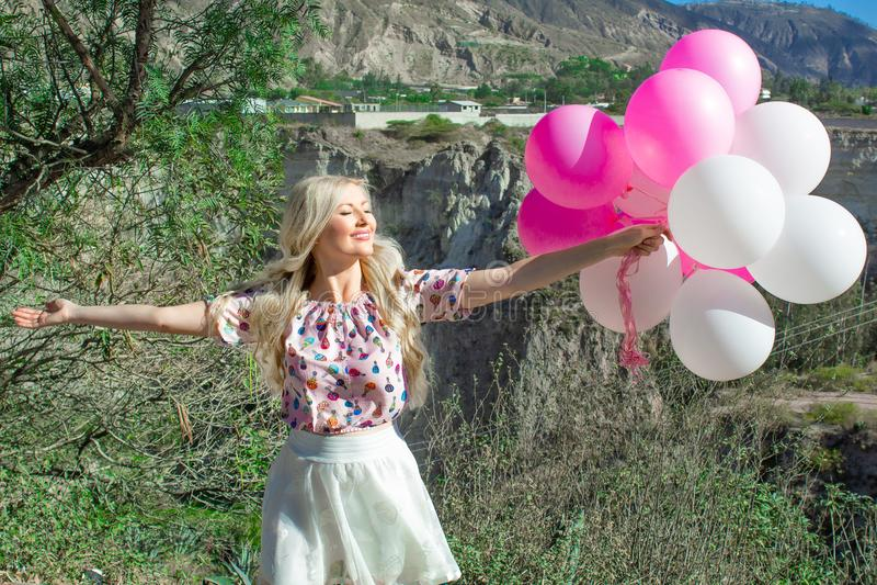 Bella donna bionda che sta e che esamina un bello paesaggio e le montagne E tiene i palloni rosa in sua mano immagine stock