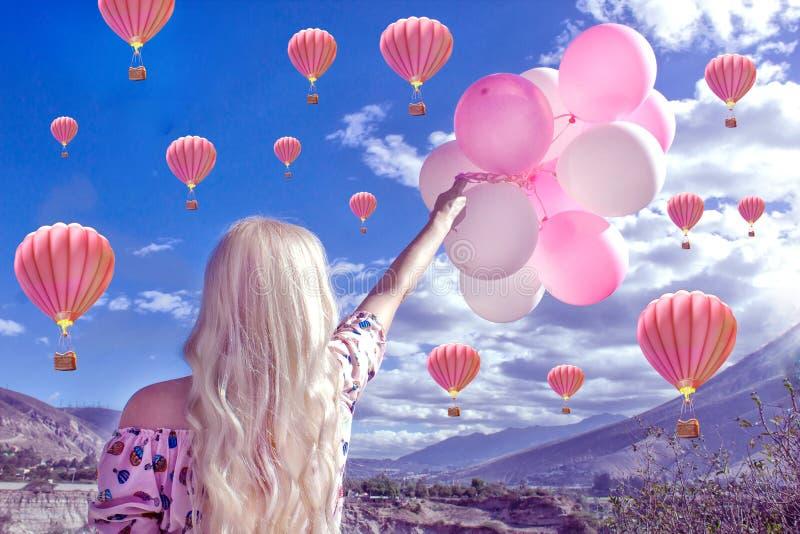 Bella donna bionda che sta e che esamina un bello paesaggio e le montagne E tiene le palle rosa in sua mano fotografie stock libere da diritti