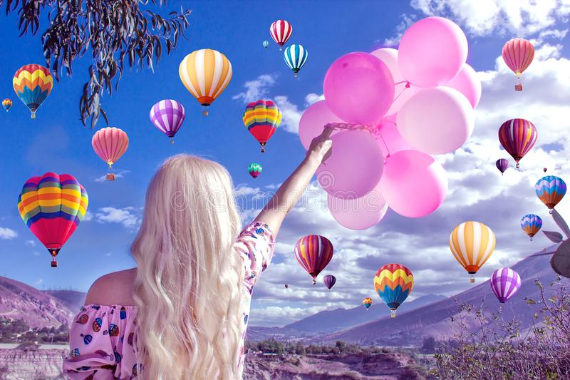 Bella donna bionda che sta e che esamina un bello paesaggio e le montagne E tiene le palle rosa in sua mano Nel cielo fotografia stock libera da diritti
