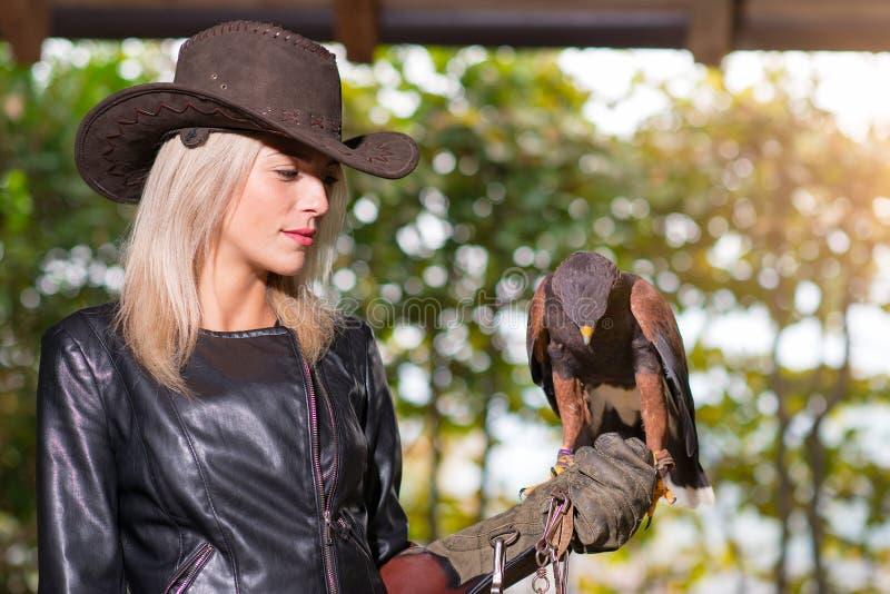 Bella donna bionda che tiene un hawkon di harris un glov protettivo immagini stock libere da diritti