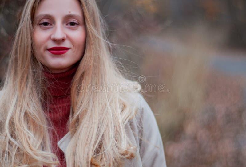 Bella donna bionda con capelli lunghi nella foresta di autunno fotografia stock libera da diritti
