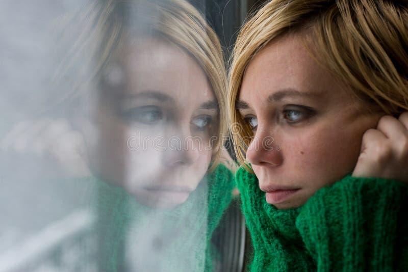 Bella donna bionda con il maglione davanti ad una finestra immagine stock