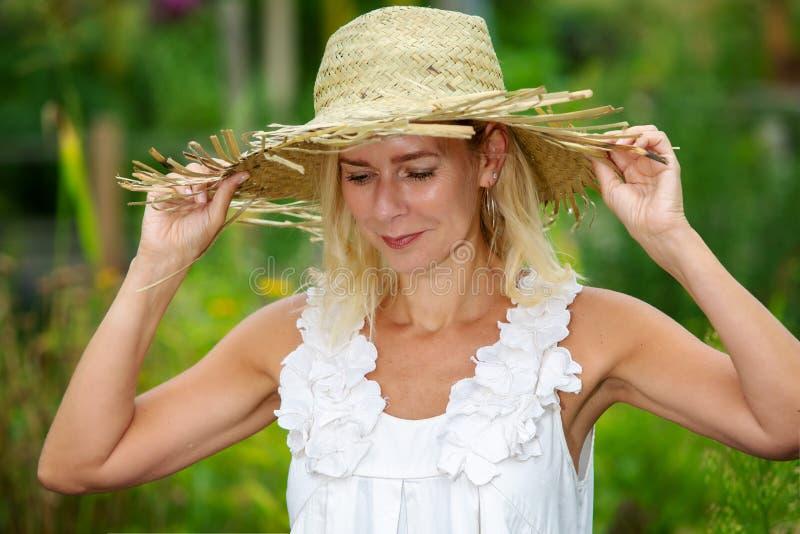 Bella donna bionda con la condizione del cappello di paglia esterna in giardino immagini stock