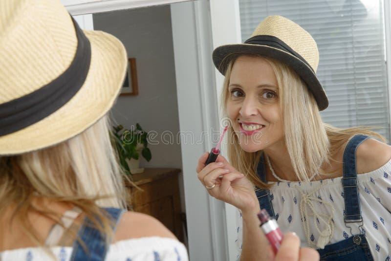 Bella donna bionda con lo specchio che mette labbro-lucentezza fotografie stock libere da diritti