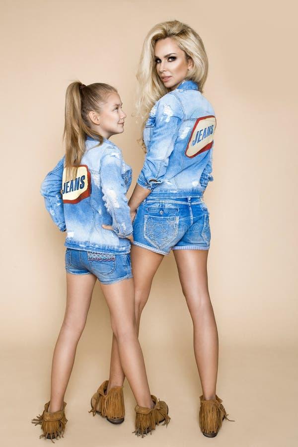 Bella donna bionda con sua figlia in un rivestimento e negli shorts del denim Modelli di moda in abbigliamento dei jeans fotografia stock