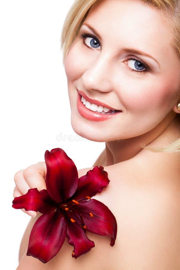 Bella donna bionda con un fiore immagine stock