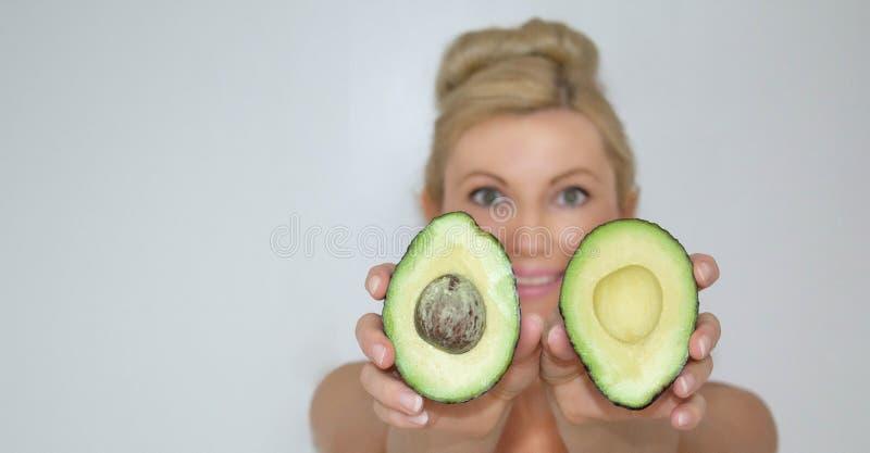 Bella donna bionda dell'avocado davanti alla macchina fotografica, primo piano fotografia stock