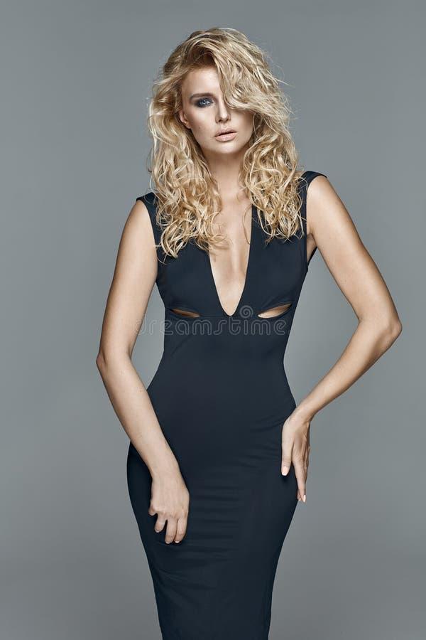Bella donna bionda di fascino in un vestito nero fotografie stock