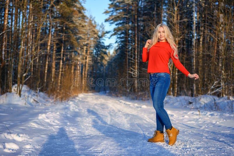 Bella donna bionda felice in maglione rosso nella foresta di inverno immagini stock