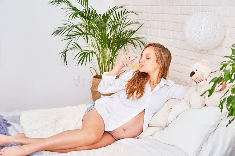 Bella donna bionda incinta che si trova sul letto in una camera da letto luminosa ragazza su un succo di frutta sorseggiante di g fotografia stock libera da diritti