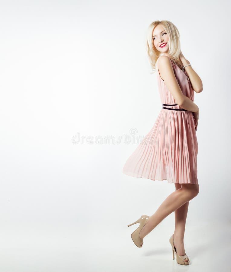Bella donna bionda notevole elegante sexy con trucco luminoso in vestito rosa con le gambe snelle di dlinnymi in studio su bianco fotografie stock libere da diritti