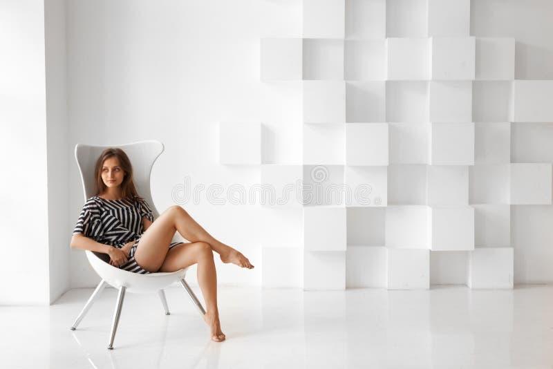 Bella donna bionda, sedentesi su una sedia immagini stock libere da diritti