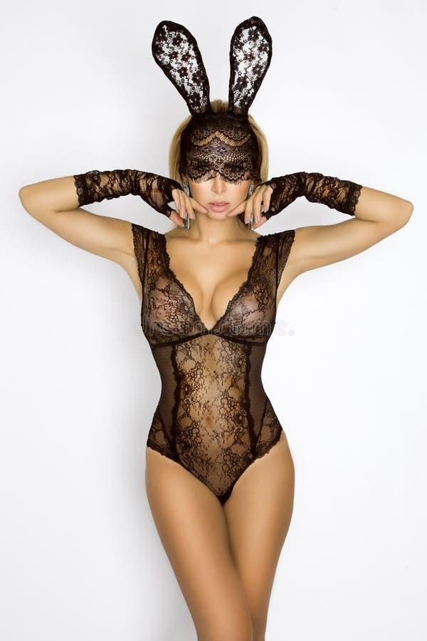 Bella, donna bionda sexy in biancheria elegante e maschera nera del coniglietto di pasqua del pizzo fotografia stock libera da diritti