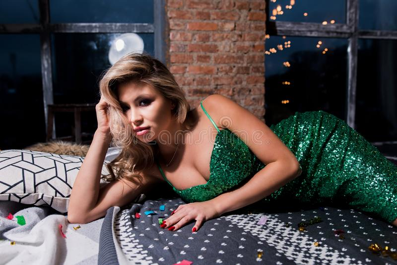 Bella donna bionda sexy in breve vestito elegante che si trova sul sofà moderno Modello di modo in vestito dorato Partito, festa fotografia stock