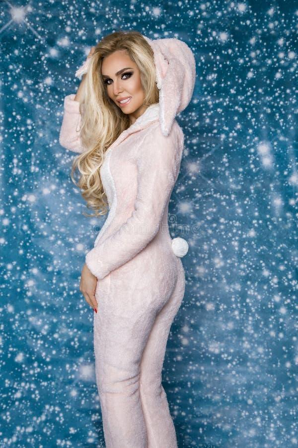 Bella donna bionda sexy che porta un pigiama, un costume del coniglietto, sorridente felicemente Modello di modo in vestito dorat immagine stock libera da diritti