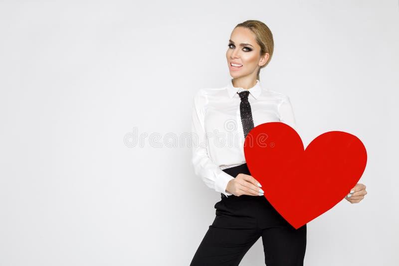 Bella, donna bionda sexy e elegante che tiene un cuore rosso del biglietto di S. Valentino immagine stock