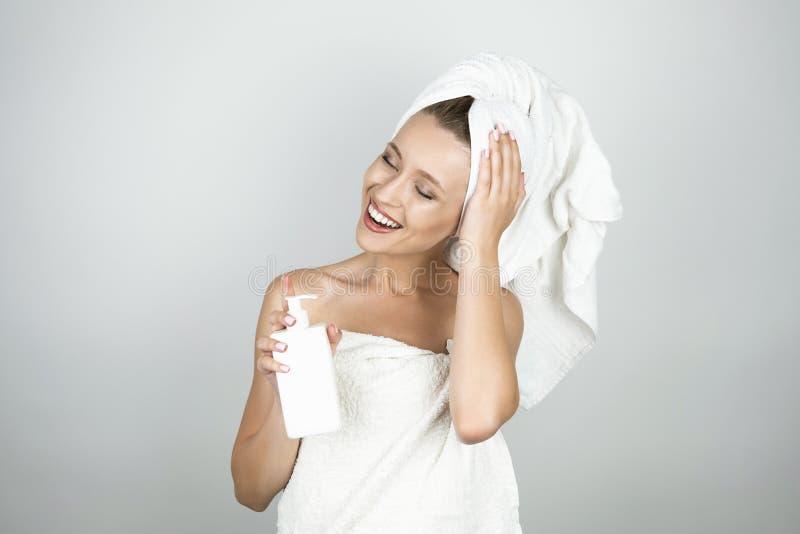 Bella donna bionda sorridente in asciugamano bianco sopra il corpo e sul suo fondo bianco isolato lozione del corpo della tenuta  fotografie stock libere da diritti