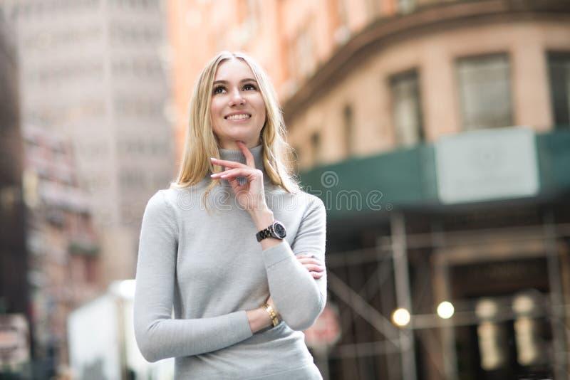 Bella donna bionda sorridente che pensa e che cammina sulla via della città immagini stock