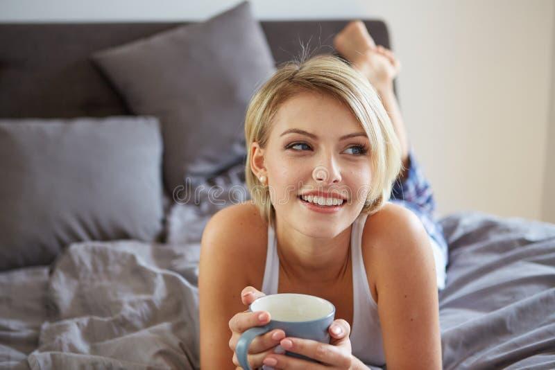Bella donna bionda sorridente felice che si sveglia con fotografie stock libere da diritti