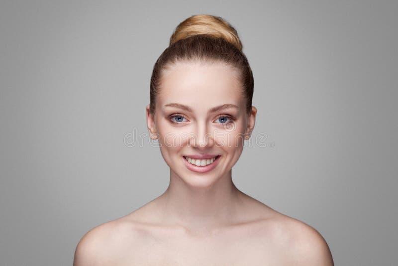 Bella donna bionda sorridente a trentadue denti felice con i capelli del panino che esaminano macchina fotografica Purezza, belle fotografia stock