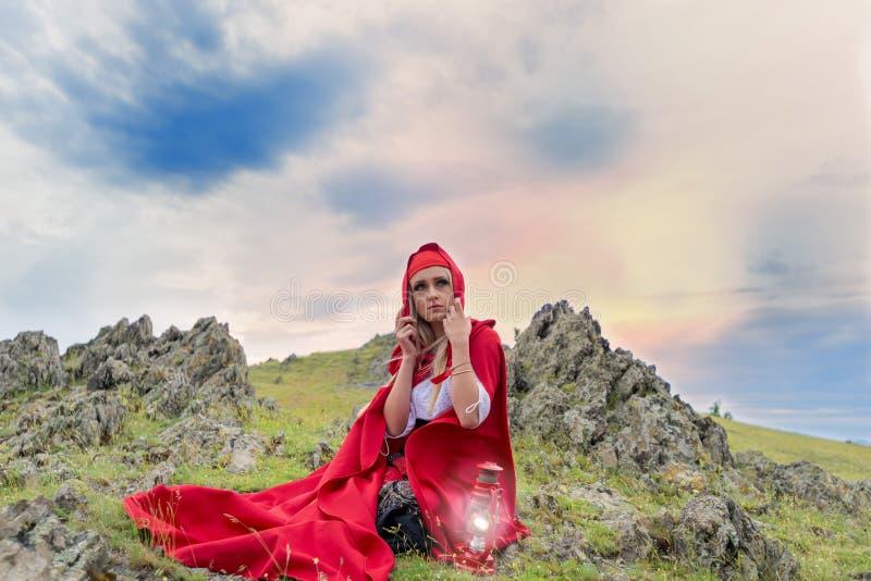 Bella donna bionda in vestito antiquato e mantello rosso che si siedono sulle rocce immagini stock libere da diritti