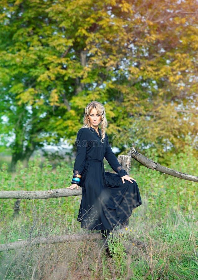 Bella donna bionda in vestito nero immagini stock