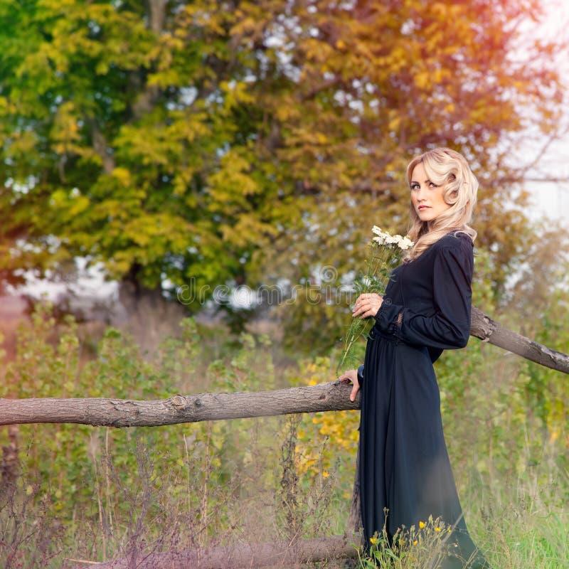 Bella donna bionda in vestito nero fotografia stock libera da diritti