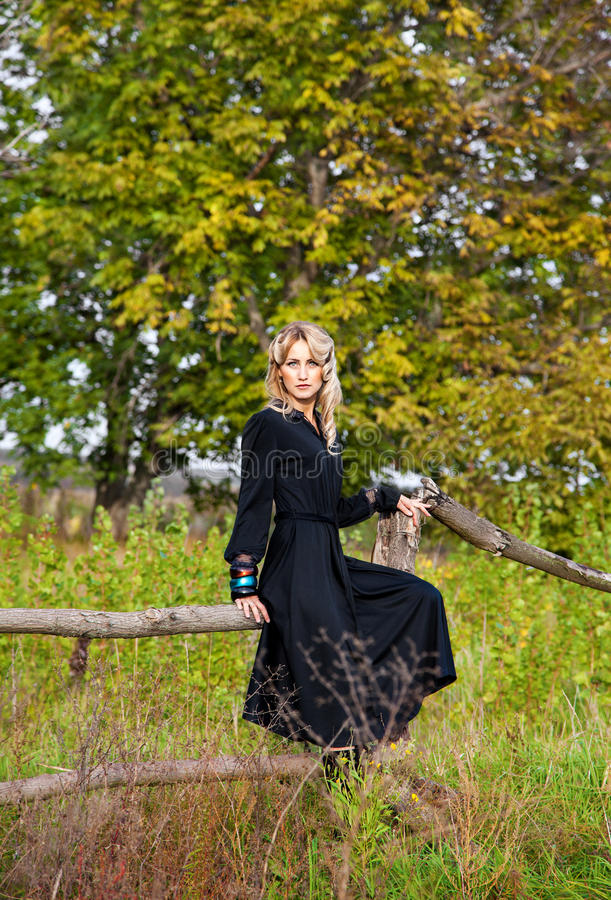 Bella donna bionda in vestito nero immagine stock