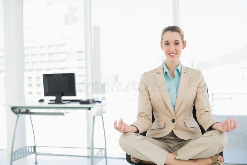Bella donna calma che si siede nella posizione di loto sulla sua poltrona girevole fotografia stock libera da diritti
