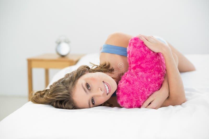 Bella donna calma che stringe a sé con il suo cuscino del cuore che si trova sul suo letto fotografia stock libera da diritti