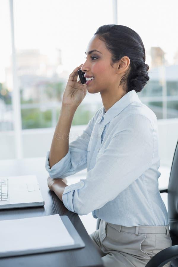 Bella donna calma che telefona con il suo smartphone che si siede al suo scrittorio immagine stock